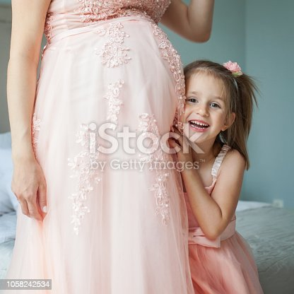 Happy daughter and pregnant mother. Little child girl and pregnant belly