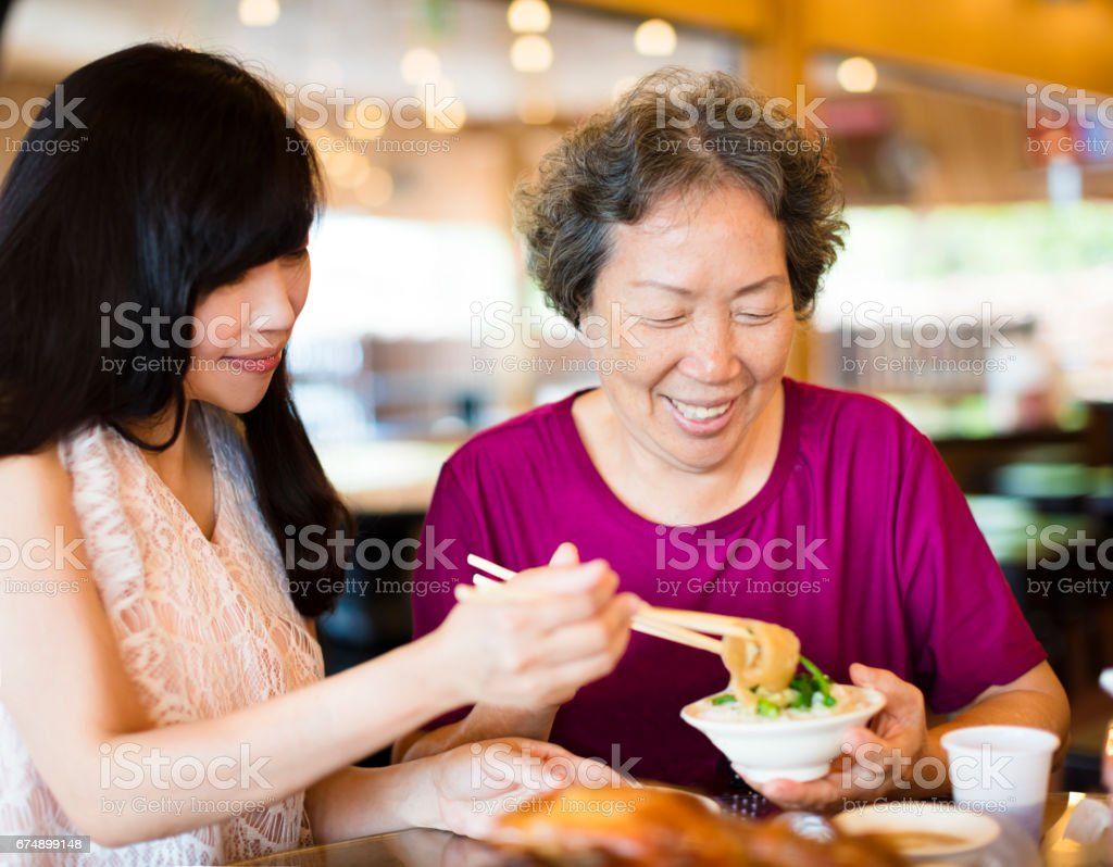 Happy  daughter and senior mother enjoy eating in restaurant stock photo