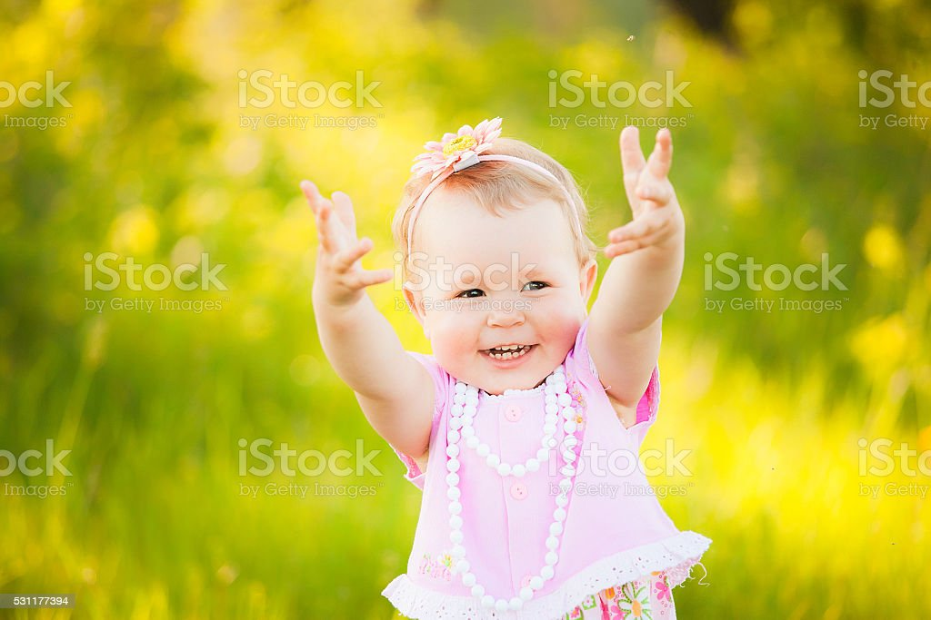 Happy daughter dressed in pink clothes playing at nature stock photo