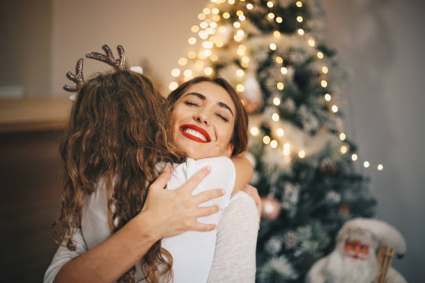 Happy daughter embracing her mother on New Year's day. stock photo