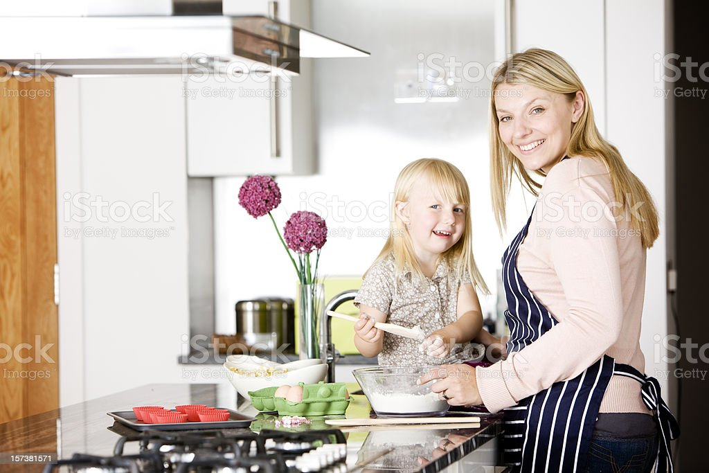 Happy daughter helping her mother baking cakes in the kitchen royalty-free stock photo