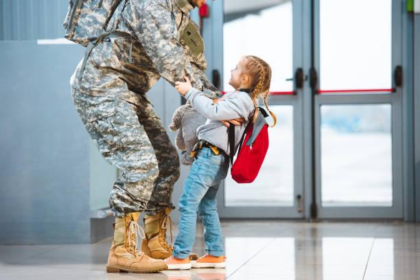 glückliche tochter holding vater in militäruniform im flughafen - camouflagekleidung mädchen stock-fotos und bilder