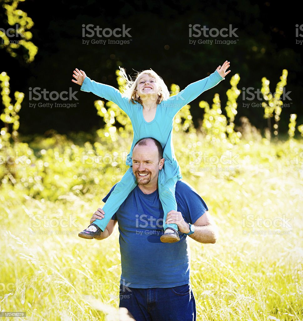 Happy daughter riding on dad's shoulders during walk in meadow stock photo