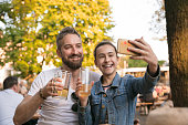 Happy daughter taking selfie through mobile phone while having drink at beer garden