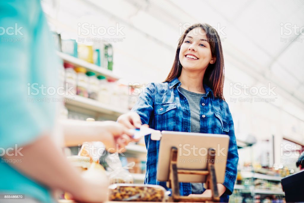 Happy deli owner receiving credit card from customer in store stock photo