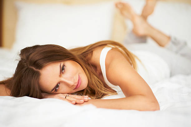 Happy delicate woman lying on bed looking into camera stock photo