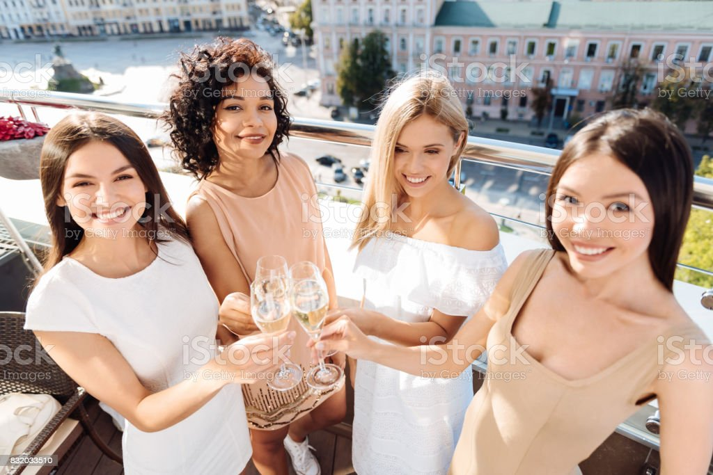 Happy delighted women raising their glasses stock photo