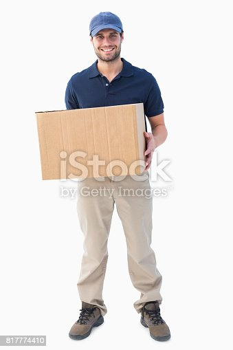 istock Happy delivery man holding cardboard box 817774410