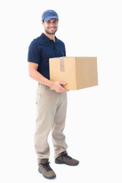 happy delivery man holding cardboard box - addetto alle consegne foto e immagini stock