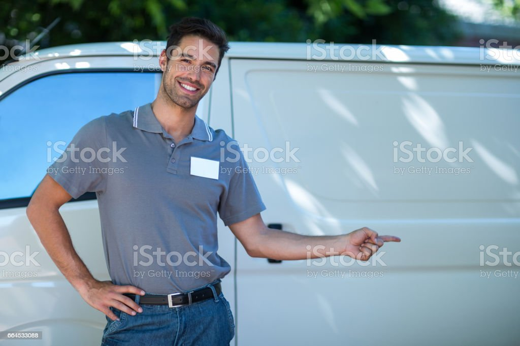 Happy delivery man pointing at van royalty-free stock photo