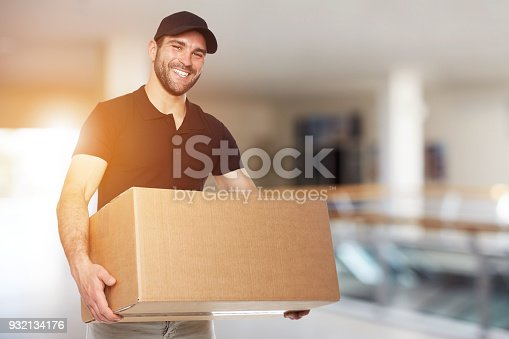 Happy delivery man with box in business center