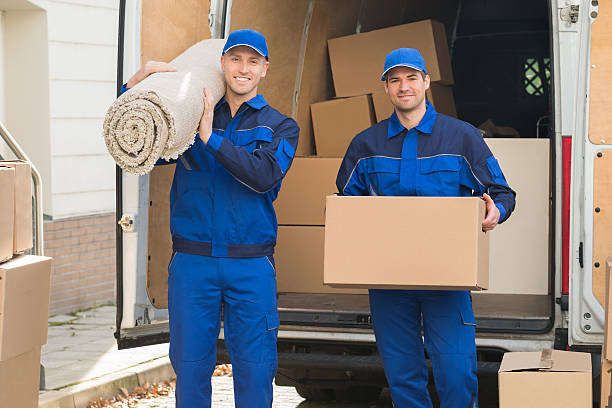 happy delivery men carrying cardboard box and carpet - umzug transport stock-fotos und bilder
