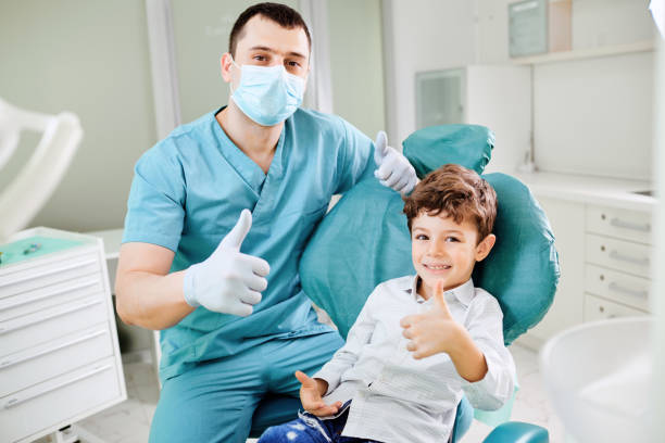 Happy dentist and child raised their thumb stock photo