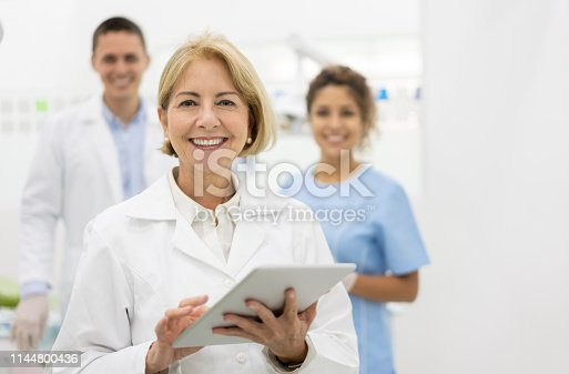 Portrait of happy dentist at the office with her team and holding a tablet computer and looking at the camera smiling