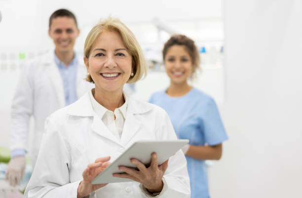 Happy dentist at the office with her team and holding a tablet computer Portrait of happy dentist at the office with her team and holding a tablet computer and looking at the camera smiling dentist stock pictures, royalty-free photos & images