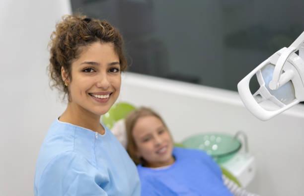 glücklicher zahnarzt prüft eine girlâs-zähne - sprechstundenhilfe stock-fotos und bilder