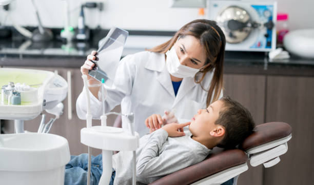 happy dentist looking at an x-ray with his young patient - dentist stock photos and pictures