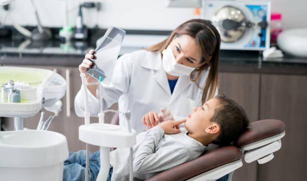 glücklich zahnarzt ein röntgenbild mit seinem jungen patienten betrachten - dentist stock-fotos und bilder