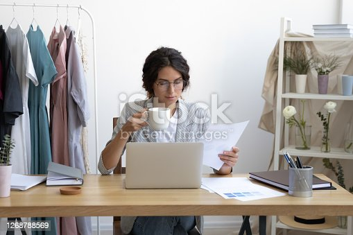 Attractive young businesswoman drinking morning cup of hot coffee, looking through financial paper documentation at workday beginning in office, happy designer enjoying break time at workplace.