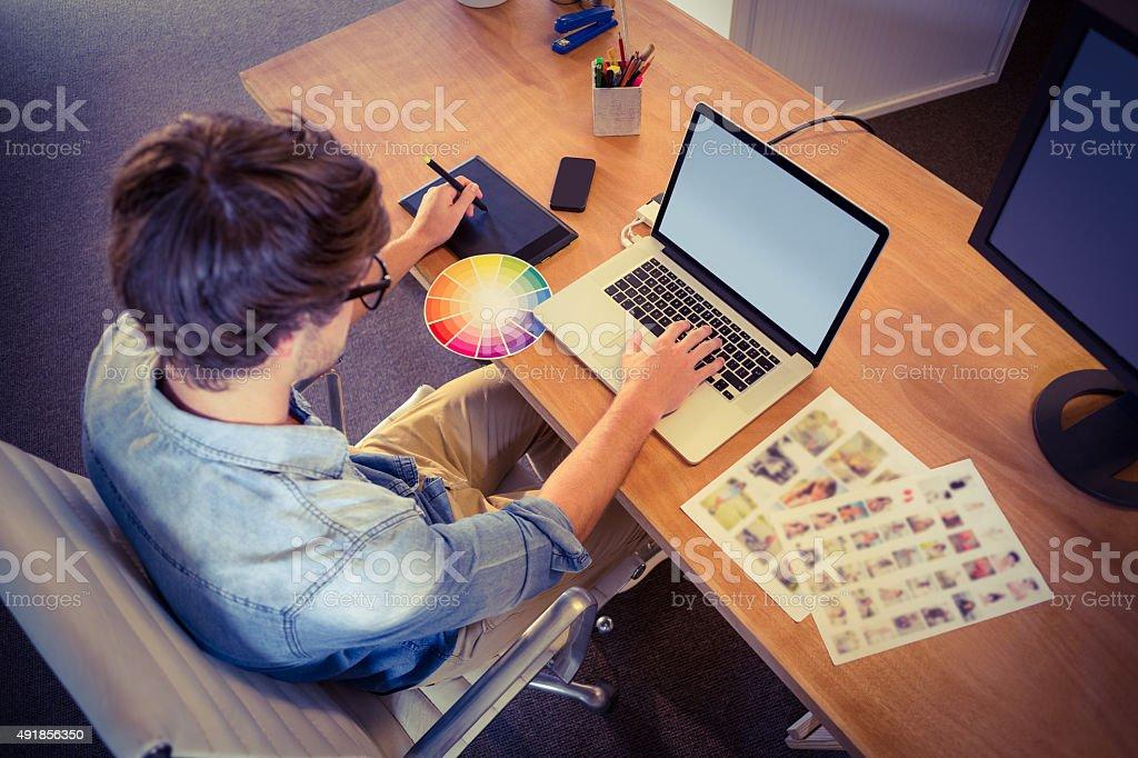 Happy designer working on his laptop stock photo