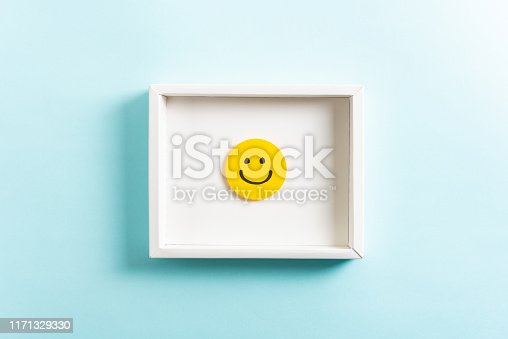 istock Happy diploma concept. Concept of well-being, well done, feedback, employee recognition award. Happy yellow smiling emoticon face frame hanging on blue background. 1171329330