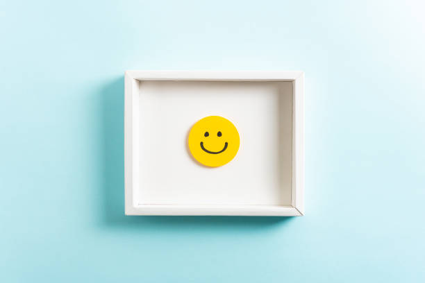 happy diploma concept. concept of well-being, well done, feedback, employee recognition award. happy yellow smiling emoticon face frame hanging on blue background. - interação com o cliente imagens e fotografias de stock