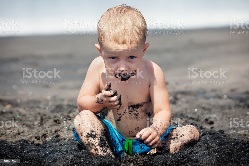 Happy dirty child play with sand on family beach vacation stock photo