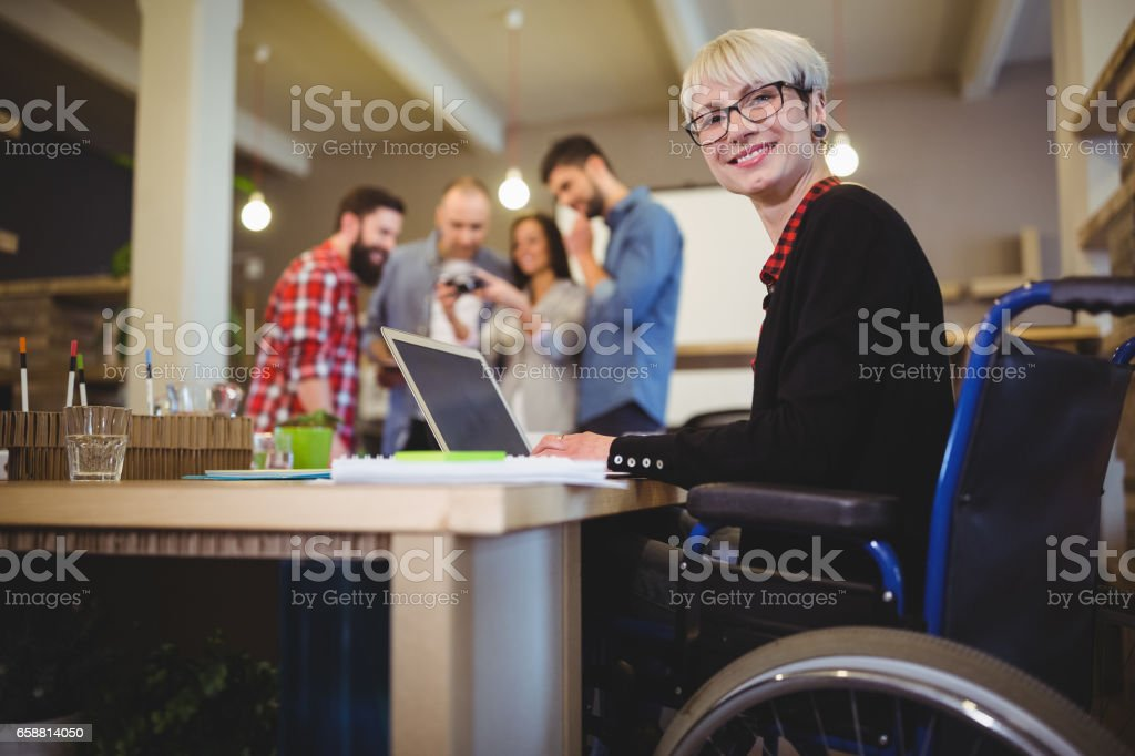Feliz empresaria con discapacidad utilizando la computadora portátil en el escritorio - foto de stock