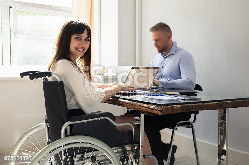1144373653 istock photo Happy Disabled Businesswoman Working On Laptop 975124372