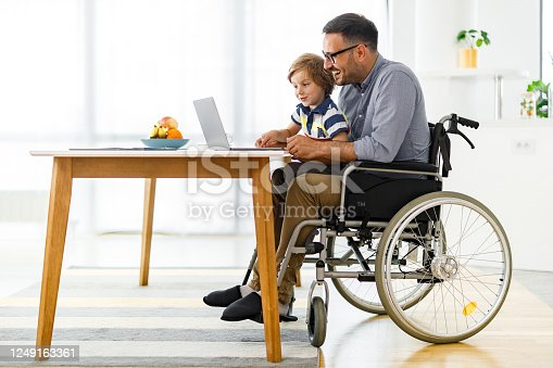 Happy single father in a wheelchair and his small son using laptop at home. Copy space.