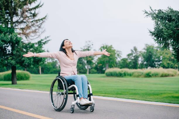 glückliche behinderte Frau im Rollstuhl gestikuliert beim Blick auf klaren Himmel – Foto