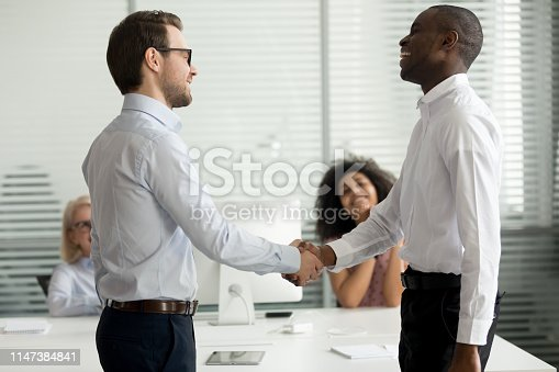 istock Happy diverse businessmen greeting each other with handshake 1147384841