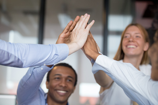 istock Happy diverse businesspeople giving high five closeup focus on hands 1127397493