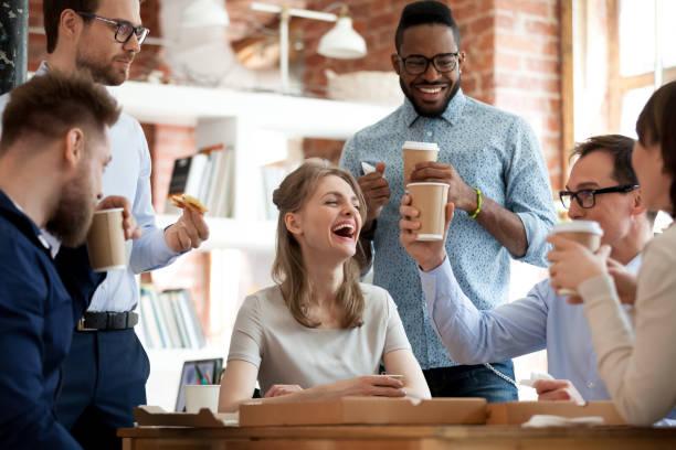 happy diverse colleagues celebrate during lunch break in office - fare una pausa foto e immagini stock