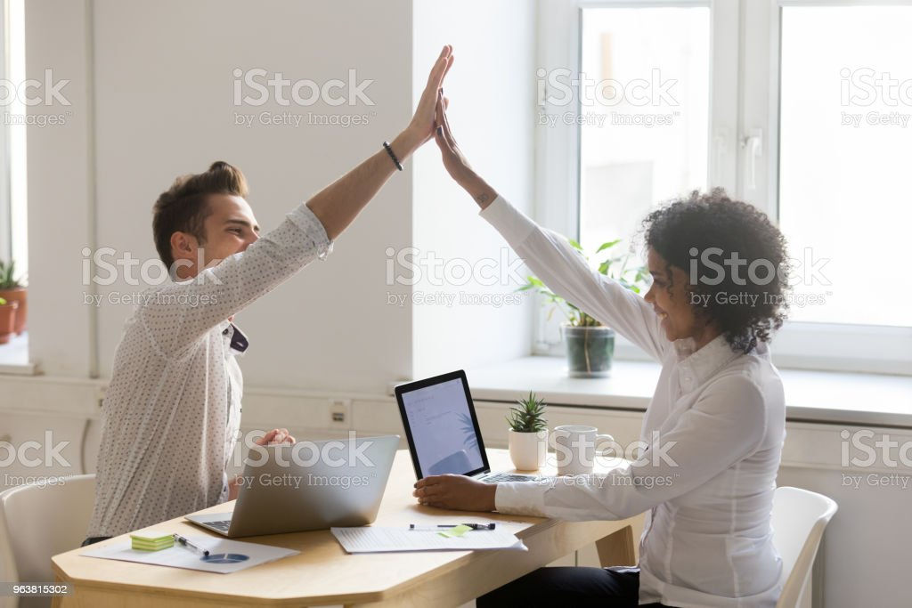 Happy diverse colleagues giving high five celebrating good teamwork result stock photo