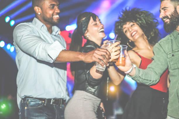 glad mångskiftande kultur vänner har fest i club på natten - ungdomar har kul hejar med drinkar på disco dansgolv - ungdomskoncept - fokus på svart man hand - vintage filter - happy indie pop bildbanksfoton och bilder