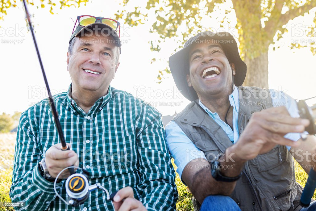 Happy diverse fishing buddies enjoy fishing together stock photo
