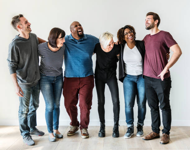 Happy diverse friends standing in a row stock photo