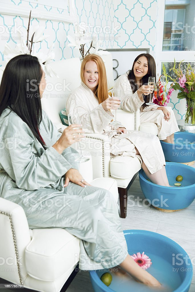Happy diverse girlfriends enjoying a spa day with champagne while...
