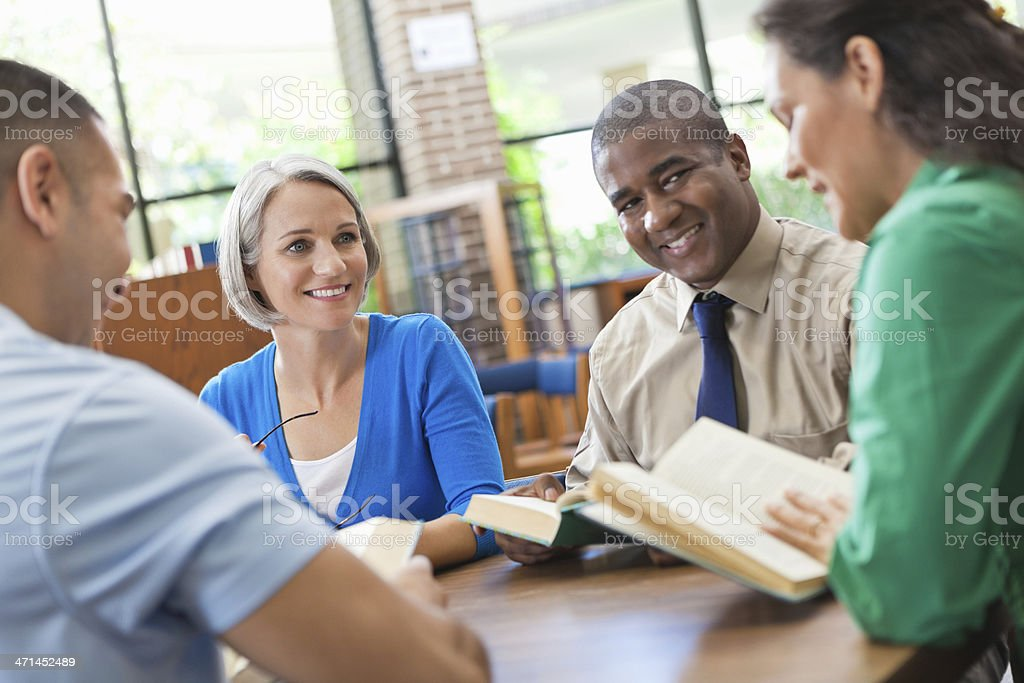 Happy diverse group of friends discussing a book in library stock photo