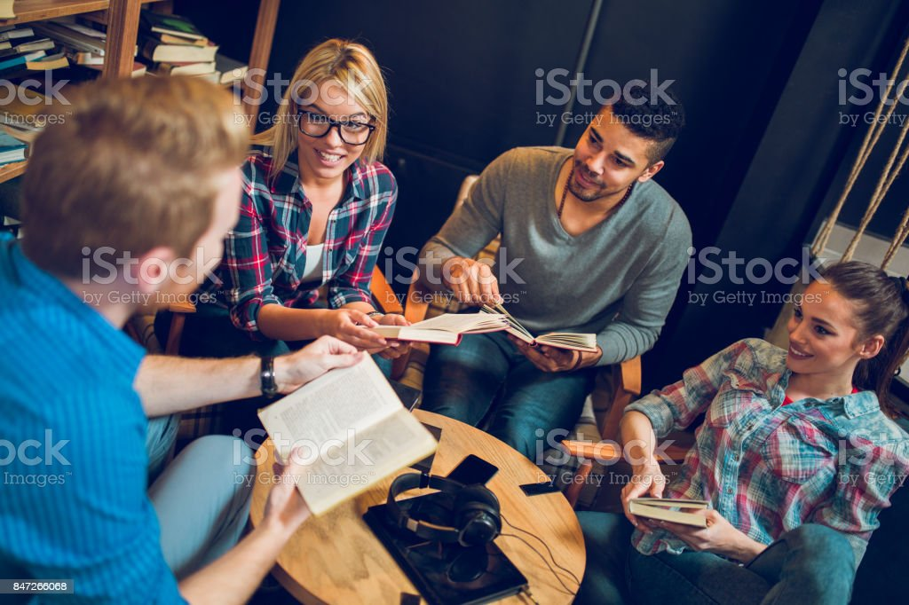 Happy diverse group of friends discussing a book in library. stock photo