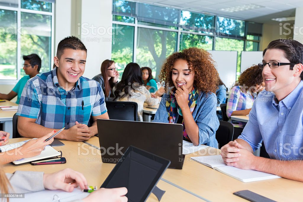 Happy diverse group of high school or college students studying stock photo
