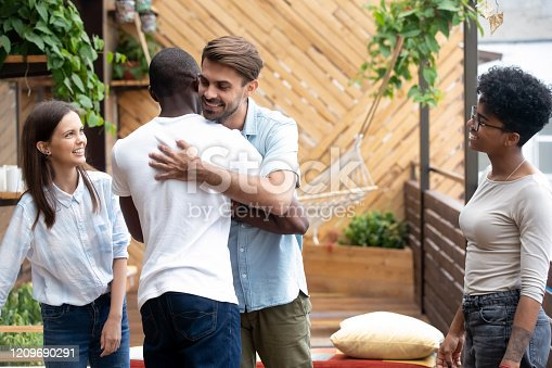 Happy multiracial male friend embrace saying hello at team or group gathering outside, smiling diverse young people greeting give hug introduce or get acquainted at friendly meeting in café or pub