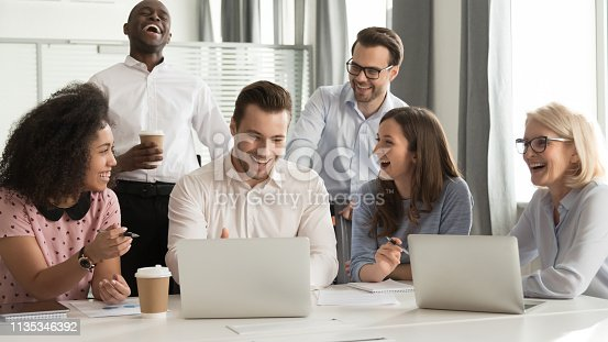 istock Happy diverse office workers team laughing together at group meeting 1135346392