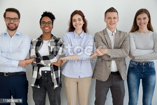 istock Happy diverse people standing holding hands together 1156088878