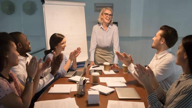 fröhliches, vielfältiges team lobt den glücklichen mentor-trainer für die präsentation - danke an lehrerin stock-fotos und bilder