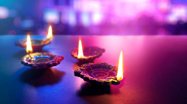 happy diwali - colorful clay diya lamps lit during diwali celebration - diwali stock pictures, royalty-free photos & images