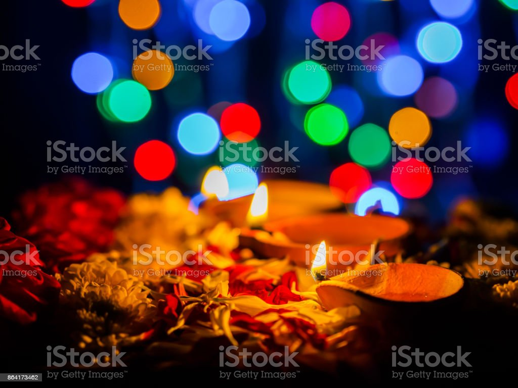 Happy Diwali - Diya lamps lit with flowers bokeh background during diwali celebration. royalty-free stock photo