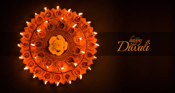 happy diwali greeting card design using beautiful clay diya lamps lit on diwali night celebration.  indian hindu light festival called diwali, a festival of light - diwali stock pictures, royalty-free photos & images