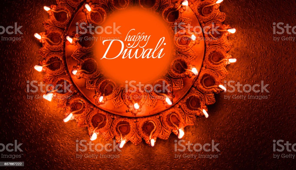 Happy Diwali greeting card design using Beautiful Clay diya lamps lit on diwali night Celebration.  Indian Hindu Light Festival called Diwali, a festival of light stock photo